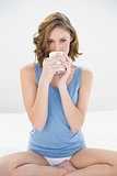 Calm attractive woman sitting on her bed drinking from white cup