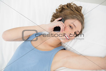 Attractive peaceful woman phoning with her smartphone lying on her bed