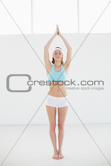 Beautiful sporty woman doing yoga pose in sports hall