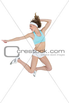 Attractive sporty woman jumping while pointing