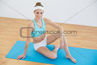 Attractive woman wearing sportswear sitting on exercise mat