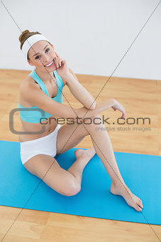 Cute woman posing sitting on blue exercise mat in sports hall