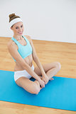 Cheerful cute woman wearing sportswear sitting on blue exercise mat