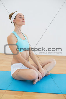 Calm sporty woman sitting on blue exercise mat meditating