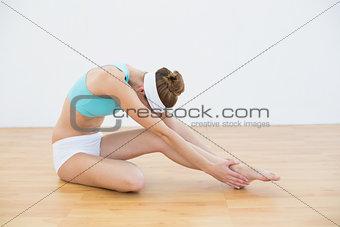 Beautiful slender woman wearing sportswear stretching her leg
