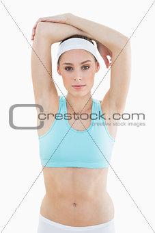 Beautiful slender woman posing lifting her arms looking at camera
