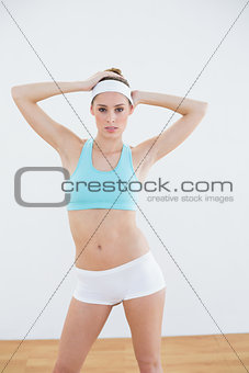 Attractive slim woman posing in sportswear looking at camera