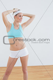 Happy sporty woman wearing sportswear posing lifting her arms