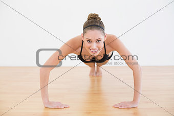 Beautiful fit woman doing press ups smiling at camera