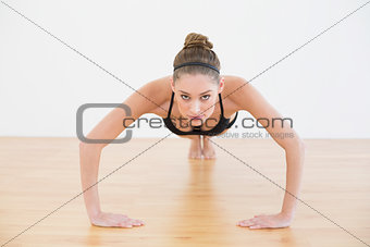 Focused sporty woman wearing sportswear doing press ups