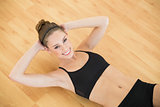 High angle view of sporty slender woman doing sit ups in sports hall