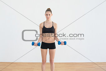 Focused toned woman lifting blue dumbbells