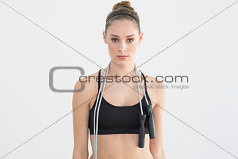 Attractive sporty woman posing holding a skipping rope