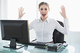 Cheering female businesswoman sitting at her desk