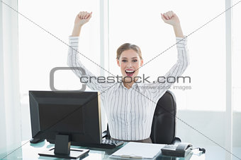 Beautiful cheering female businesswoman sitting at her desk