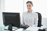 Gorgeous smiling businesswoman working on her computer