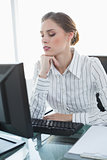 Young serious businesswoman sitting at her desk