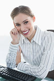 Cheerful chic businesswoman sitting at her desk smiling at camera