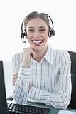 Laughing chic agent wearing headset sitting at her desk