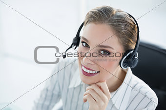 Beautiful smiling agent wearing headset sitting at her desk