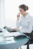 Concentrated female agent sitting at her desk wearing headset