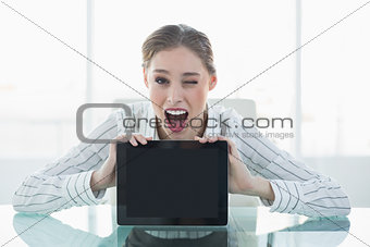 Beautiful happy businesswoman showing tablet blinking her eye