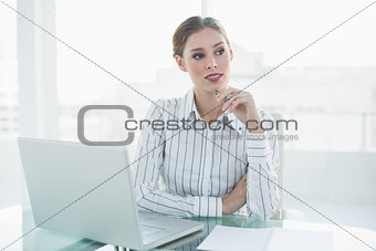 Thoughtful lovely businesswoman sitting at her desk holding a pencil