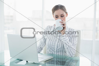Beautiful businesswoman sitting at her desk drinking from cup