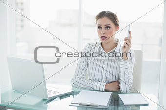 Beautiful thinking businesswoman holding a pen sitting at her desk