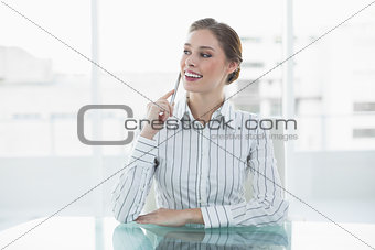 Beautiful thinking businesswoman sitting at her desk