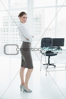 Attractive peaceful businesswoman posing standing in her office
