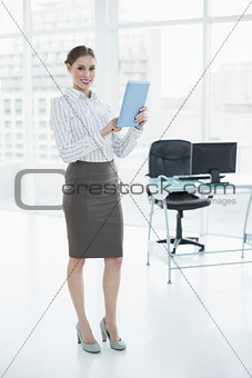 Beautiful calm businesswoman holding her tablet standing in her office