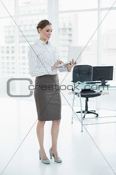 Attractive calm businesswoman working with her notebook