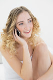 Pretty cheerful blonde sitting on bed phoning