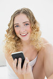 Pretty blonde sitting on bed holding smartphone