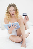 Pretty excited blonde sitting on bed holding tablet and credit card