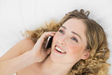 Pretty happy blonde lying on bed phoning with mobile phone