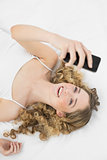Pretty smiling blonde lying on bed holding mobile phone
