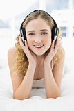 Pretty cheerful blonde lying in bed listening to music
