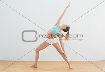 Calm slim blonde standing in high lunge pose