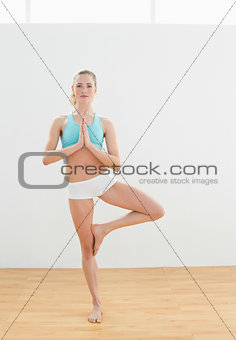 Calm slim blonde standing in eagle pose