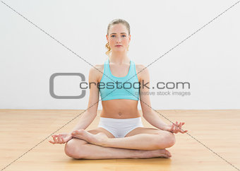 Calm slim blonde sitting in lotus pose
