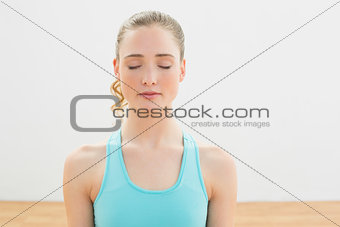 Calm slim blonde sitting on floor with closed eyes