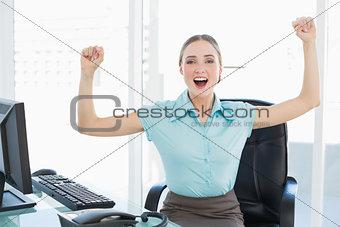 Classy cheerful businesswoman cheering with raised arms