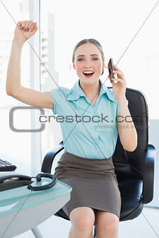 Classy cheerful businesswoman on the phone cheering with raised arms