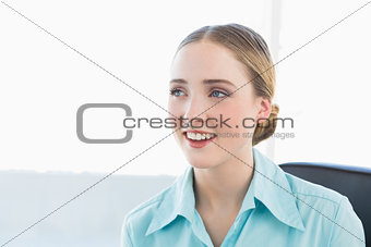Classy smiling businesswoman looking away