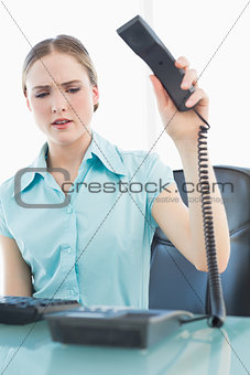 Classy angry businesswoman hanging up phone