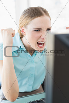 Classy excited businesswoman sitting in front of computer