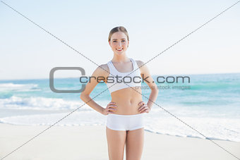 Smiling slender woman standing hands on hips