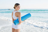 Lucky slender woman holding rolled up exercise mat